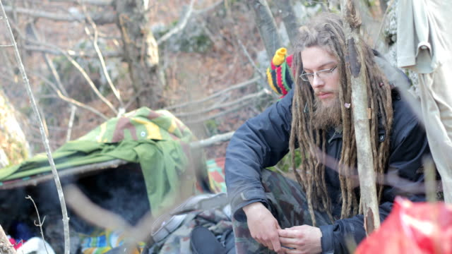 Young Adult Man with Dreadlocks Camping in Nature Young Adult Man with Dreadlocks Camping in Nature. homeless shelter stock videos & royalty-free footage