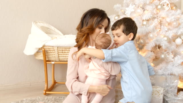 Young adult mother with her children in Christmas time at home video
