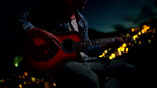Young adult playing guitar on rooftop with Skyline background video