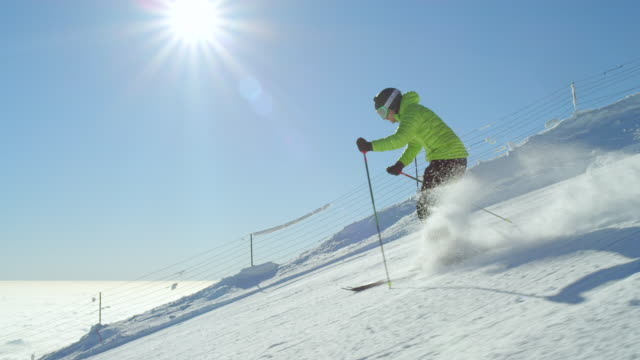 SLOW MOTION FOLLOW: Young adult skier enjoy first track on fresh groomed piste video