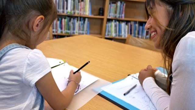 Young adult teacher helps young schoolgirl with writing assignment