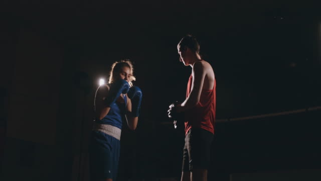 Young adult woman doing kickboxing training with her coach