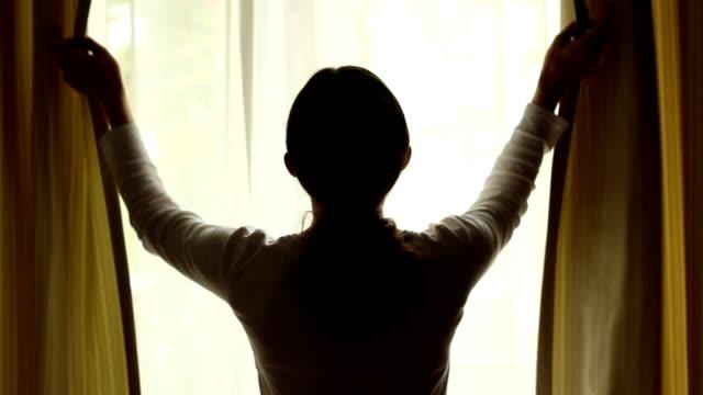 vídeos y material grabado en eventos de stock de adulto joven mujer de premios cortinas y bloquea la luz en la habitación. - cortina