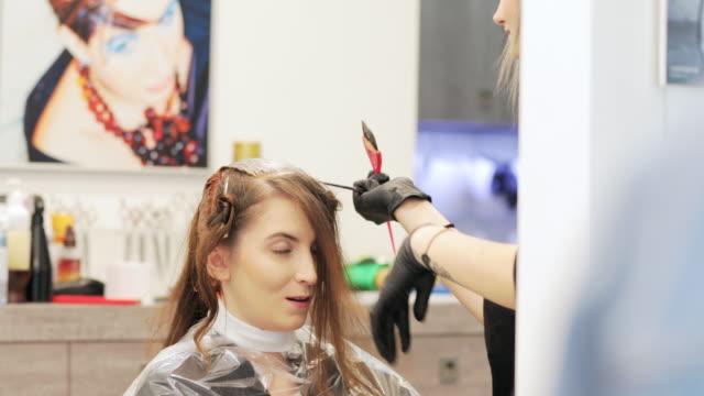 junge frau sterbehaar im friseursalon - haartönung stock-videos und b-roll-filmmaterial