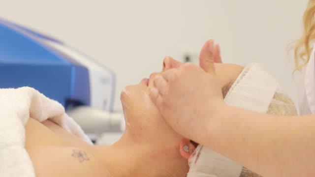 vidéos et rushes de jeune femme adulte profitant de soin de beauté au dermatologue - allongé sur le dos
