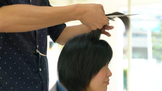 彼女の髪を得る若い成人女性カットし、スタイルのサロンで - 美容院点の映像素材/bロール
