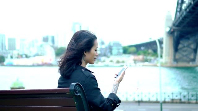 Jovem adulta ter uma pausa e procurando algo sobre tablet digital ao lado de Sydney Harbour Bridge - vídeo