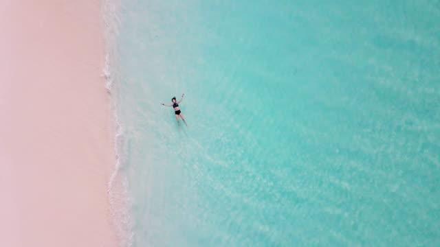 vídeos de stock, filmes e b-roll de mulher adulta nova que encontra-se para baixo em uma água do turquesa do paradisíacas em maldives - azul turquesa