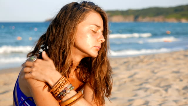 Young adult woman on the beach having problems or issues contemplating video