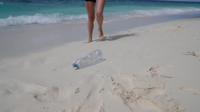 junge erwachsene frau holt einige verlassene plastikflaschen am strand - pflücken stock-videos und b-roll-filmmaterial
