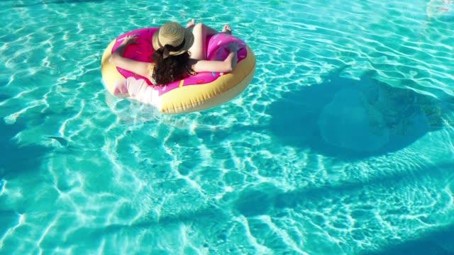 vídeos de stock, filmes e b-roll de adulta jovem, relaxando-se flutuando na água - inflável