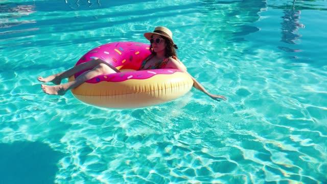 vídeos de stock, filmes e b-roll de adulta jovem, relaxando-se flutuando na água - flutuando na água