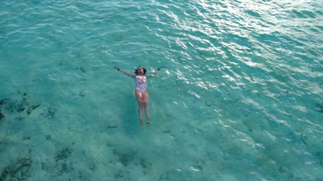 Young adult woman relaxing in the sea Young adult woman relaxing in the sea sunbathing stock videos & royalty-free footage