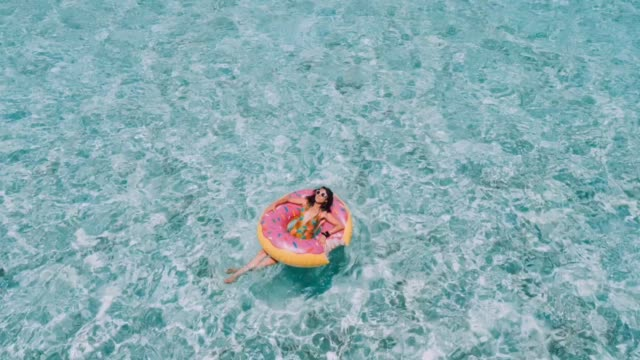 Young adult woman relaxing on inflatable in the sea Young adult woman relaxing on inflatable in the sea sunbathing stock videos & royalty-free footage