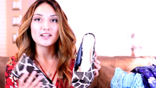 Young adult woman vlogging about fashionable clothes and shoes. video