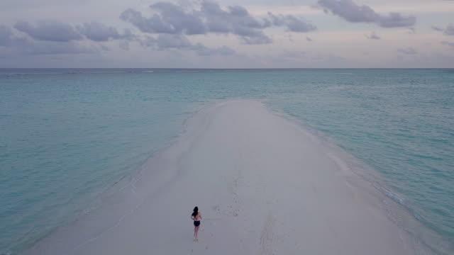 vídeos de stock, filmes e b-roll de mulher adulta nova que anda em um sandbank de encontro à água de turquesa em maldives - azul turquesa