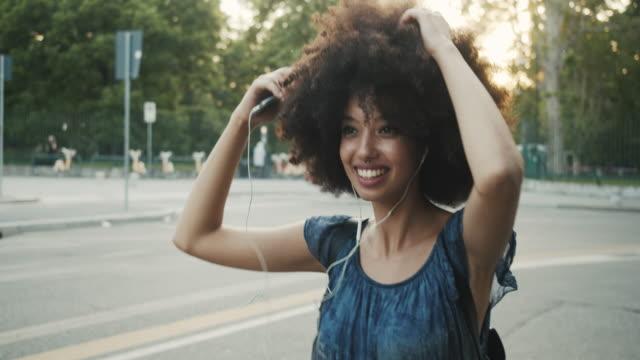 stockvideo's en b-roll-footage met jonge volwassen vrouw met afro haar dansen in de stad bij zonsondergang tijdens het luisteren naar muziek - twilight
