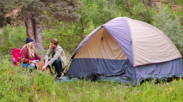 young adults camping in the wilderness - турист с рюкзаком стоковые видео и кадры b-roll