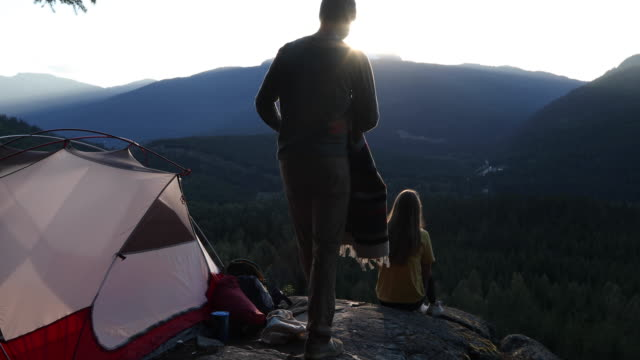 젊은 성인은 계곡 위의 바위 석판에서 캠핑 경험을 즐길 수 있습니다. - mountain top 스톡 비디오 및 b-롤 화면