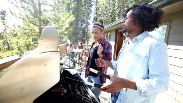Young adults enjoy dancing while grilling outdoors video