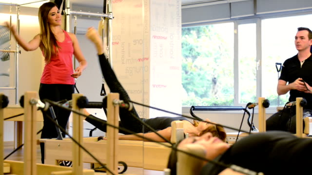 Young adults exercising at pilates club video
