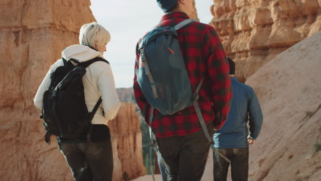4k uhd: young adults hiking into bryce canyon - utah video stock e b–roll