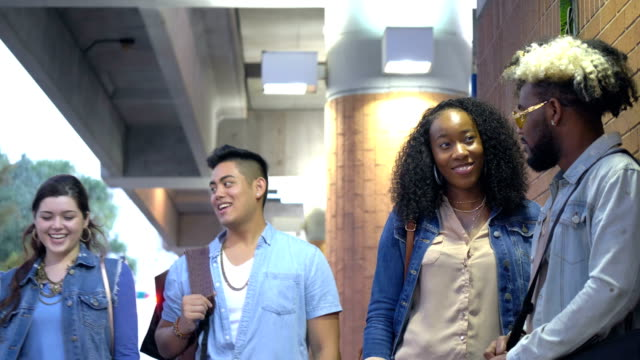 Young adults in the city, couple talking A small group of multi-ethnic adults in the city. A young African-American couple is talking in the foreground as another couple walks by them. physical position stock videos & royalty-free footage