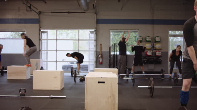 Young adults participating in various cross training routines Young adults participating in various cross training routines in a gym cross training stock videos & royalty-free footage