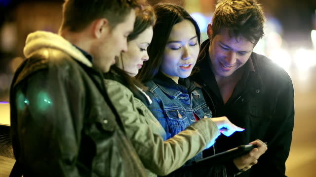 Young adults play with tablet in big city at night video