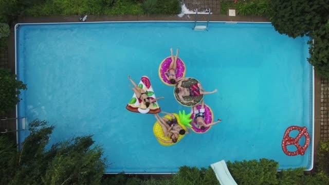 vídeos de stock, filmes e b-roll de jovens adultos piscina festa arial summer grupo parte 4 - piscina