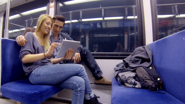 Young adults riding subway and playing with tablet video