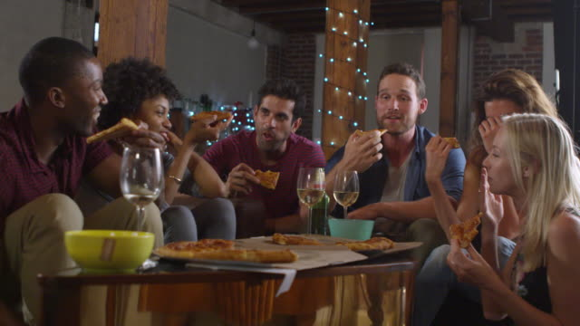 Young adults sharing pizzas at a party at home, shot on R3D video
