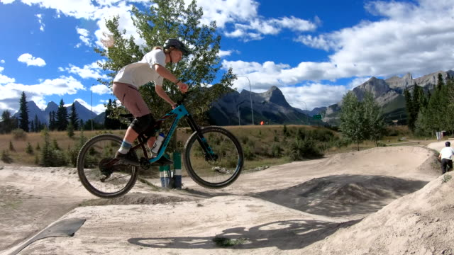 Young adults take bike jumps in mountain park