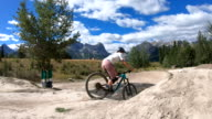 istock Young adults take bike jumps in mountain park 1271338174