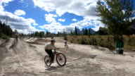 istock Young adults take bike jumps in mountain park 1271340875