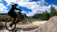 istock Young adults take bike jumps in mountain park 1271384785