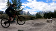 istock Young adults take bike jumps in mountain park 1271388120