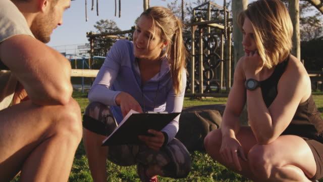 vídeos de stock, filmes e b-roll de treinamento dos adultos novos em um bootcamp ao ar livre da ginástica - personal trainer