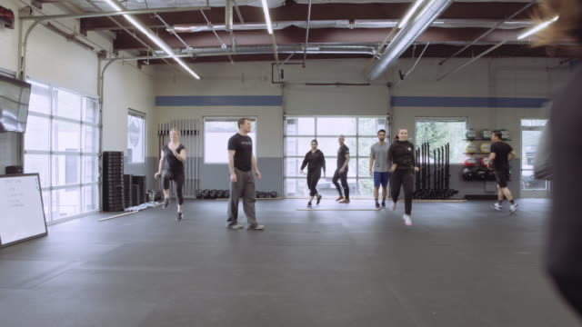 Young adults warming up with high knees exercise video