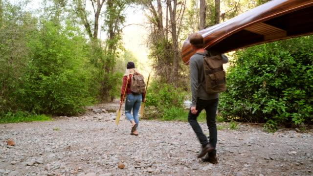 junge erwachsene mit einem kanu in der wildnis - kanu stock-videos und b-roll-filmmaterial