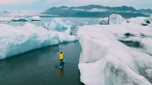 Young adventurous man paddling stand up paddle boarding through icebergs in glacier lake in Iceland