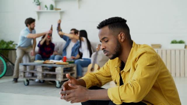 unga afrikanska amerikansk människa känner upprörd och isolerade medan vännerna fira fest hemma inomhus - avskildhet bildbanksvideor och videomaterial från bakom kulisserna