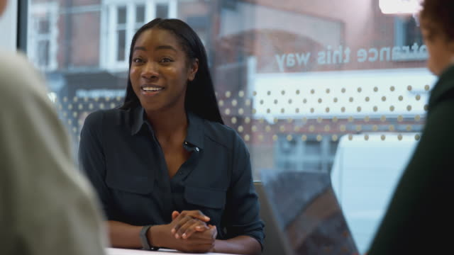 Young African American Businesswoman Sitting At Table In Office Meeting Room