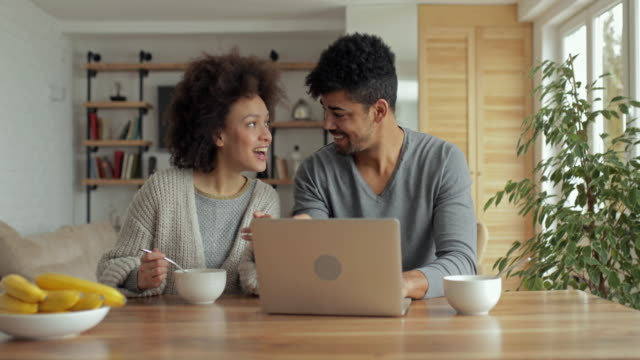 young african american couple having fun while surfing the net on laptop at home. - surfować po internecie filmów i materiałów b-roll