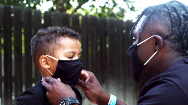 年輕的非洲裔美國爸爸説明他三歲的混合種族的兒子把他的個人保護面具在他的臉上,以防禦科維德-19冠狀病毒大流行蔓延。 - 非裔美國人種 個影片檔及 b 捲影像