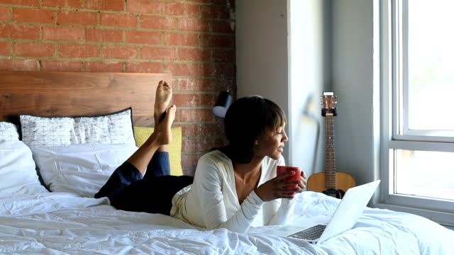 Young African American female in Bed with Coffee and Laptop video