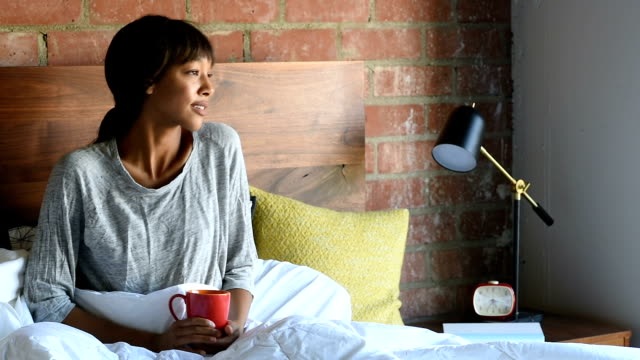 Young African American female in Bed with Coffee video