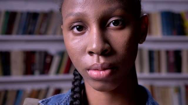Young african american female student looking into camera and standing in library, serious and concerned