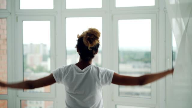 genç afro-amerikan kız evde pencere için yürüyüş ve perdeleri ayrılık sonra penceresinden manzarayı. konut, insanlar ve yaşam tarzı kavramı. - sabah stok videoları ve detay görüntü çekimi