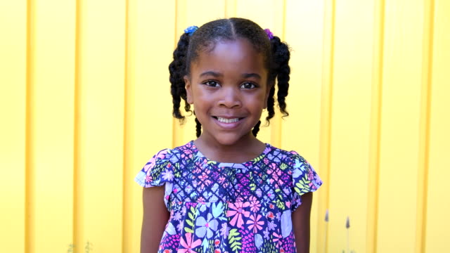 Young African American girl smiling and looking serious video